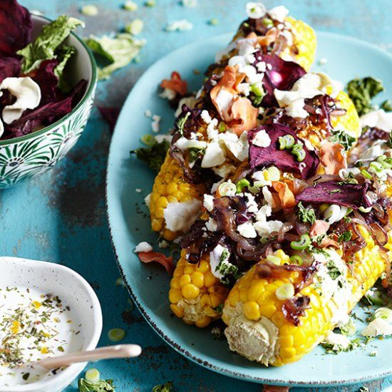 Jazz up your corn on the cob with caramelized red onions, vegetable chips, sour cream and feta cheese. (in German)
