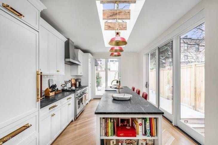 A sneak peek into the $8 million Brooklyn brownstone of celeb power couple John Krasinski and Emily Blunt. The chef's kitchen is sure to make anyone jealous with its floor-to-ceiling windows, sliding doors, and a skylight that all allow natural light to flood the kitchen. The kitchen has a gigantic center island and a Rohl porcelain sink.