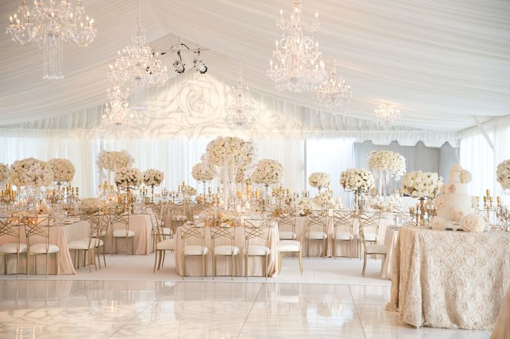The bride and groom desired a neutral color palette of cream and blush for their wedding reception. A white tent decorated with glistening chandeliers was filled with tables covered in soft pink linens and towering arrangements of ivory blooms. #white #gold #weddingreception #tent #chandeliers Photography: Aaron Delesie Photographer. Read More: http://www.insideweddings.com/weddings/elegant-all-white-country-club-wedding-with-natural-greenery/530/
