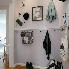 druciany czarny kosz ,ozdobne listwy z haczykami na ubrania,czarne metalowe wieszaki wiszące pojedynczo na białej ścianie w małym przedpokoj...