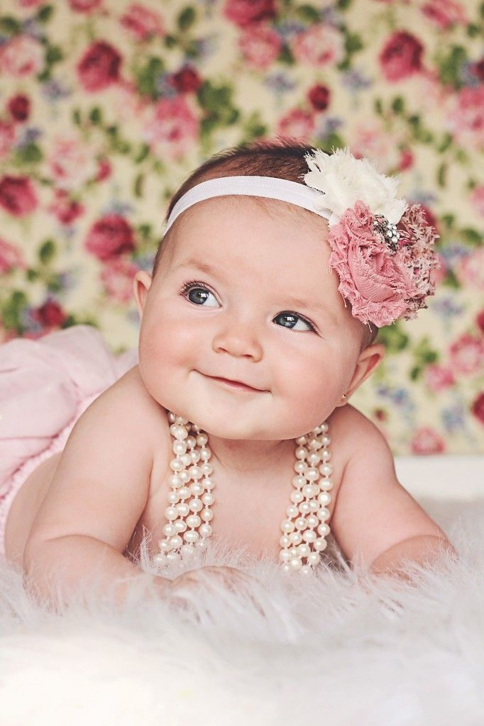 All smiles during her Vintage Floral baby photoshoot | Iliasis Muniz Photography Vintage photoshoot, floral backdrop, baby girl vintage outfits, floral baby girl headbands, pearls, pink themed photoshoot.
