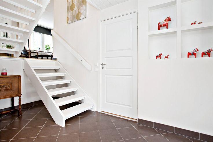 Möblerbar entréhall med plats för kläder och skor. Klinker med golvvärme och väggar målade i Stockholmsvitt. Fönster invid entrédörr och spottar i taket. Vitmålad trappa till vardagsrummet. Tvättstuga med grovingång är praktiskt placerad i direkt anslutning till entréhallen.