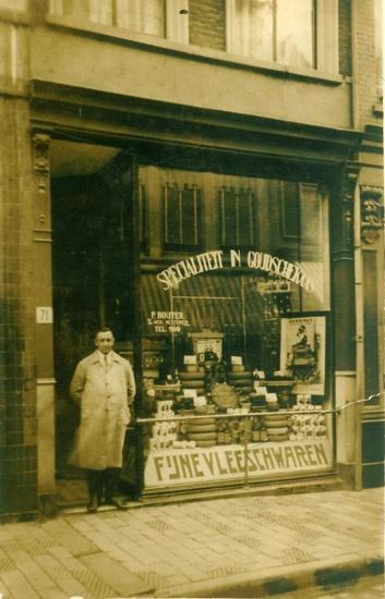 """Lange Hezelstraat 71 van de winkel van de heer Pieter Bouter. Deze zaak verkocht Fijne vleeswaren en kazen en stond bekend onder de naam: """"De Koperen Stang"""", genoemd naar de stang die als bescherming dient voor de grote winkelruit. Op de foto is deze stang goed te zien. De heer Bouter is deze zaak in 1904 begonnen. In 1959 is deze zaak overgenomen door Jan en Miep v.d. Heuvel-Heijmans . In 1993 zijn deze mensen met de zaak gestopt."""