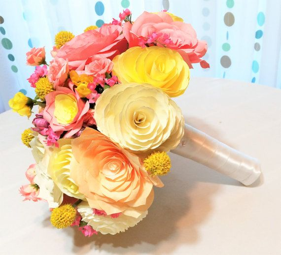 This lovely bouquet uses handmade yellow, coral and peach coffee filter paper roses and peonies. Mixed in are yellow and pink silk accent flowers. The handle is wrapped in white satin ribbon with pearl pins. Large size shown. Please contact us for smaller sizes, different colors or package prices.  • Large bouquet is 12 to 13 inches wide.  Please contact us if you would like different colors or sizes, matching boutonnieres, corsages, cake flowers, coordinating centerpieces or package…