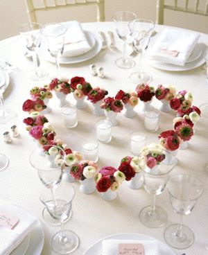 One that caught my attention was this adorable centerpiece using simple white egg cups with ranunculus arranged in a heart shape. It's a beautiful DIY centerpiece idea, affordable and very unique! I think the little egg cup idea would be adorable for escort cards as well! Set up a display of interlocking hearts, and place a small name tag in each. Very cute.