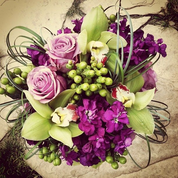 Purple, lavender, and green bouquet featuring orchids, roses, stock, and hypericum. #Purple Weddings