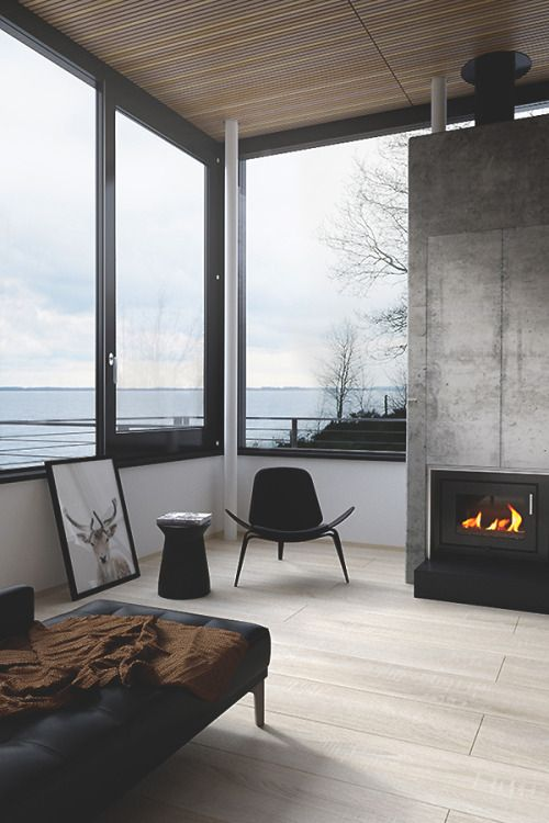 This minimally designed space highlights fire & water. A small black fireplace set in a cement wall makes this space feel cozy, while windows provide a view of the water.