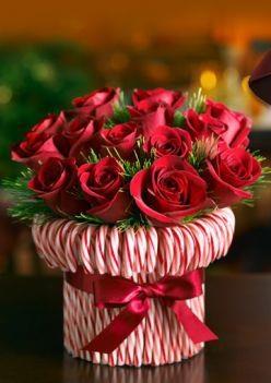 Jarrón bastón de caramelo Extiende una banda de goma alrededor de un florero cilíndrico, a continuación, se pega en los bastones de caramelo hasta que usted no puede ver el jarrón. Ate una cinta roja de seda para ocultar la cinta de goma. Rellenar con rosas o claveles rojos y blancos.