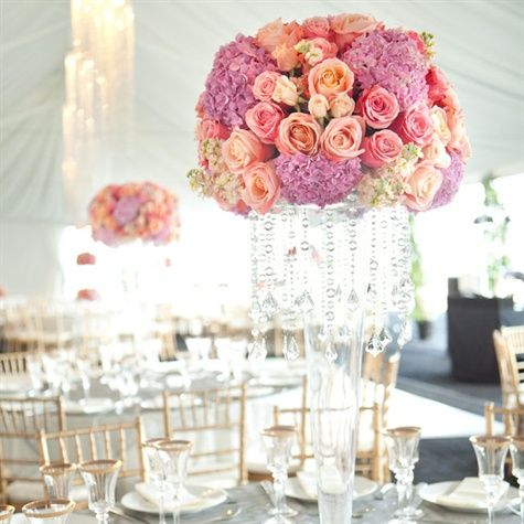 Tall vases overflowing with purple hydrangeas and pink and coral roses were draped with crystals for a luxe look.
