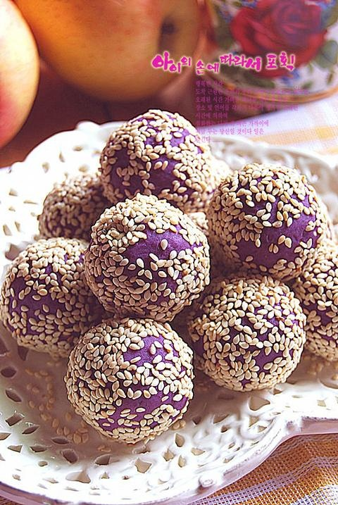 Purple sweet potato, condensed milk, white sesame, red bean paste, green bean paste   Boil peeled purple potato & let cool. Mash potato; add the appropriate amount of condensed milk; toast sesame seeds in oven; purple mashed potatoes evenly divided into small pieces, knead into ball; fillings (red bean paste, green been paste) also divided into small pieces and slightly smaller than the purple sweet potato mud knead into ball; take a purple potato balls press into the cake; roll balls in…