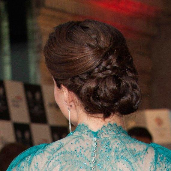 Revêtue d'une robe de dentelle turquoise, Kate Middleton porte ici un joli chignon qui intègre une tresse. Ce chignon est assez volumineux et recouvre tout l'arrière de sa tête. Pour bien dégager son ravissant visage, ses cheveux ont tous été tirés vers l'arrière.