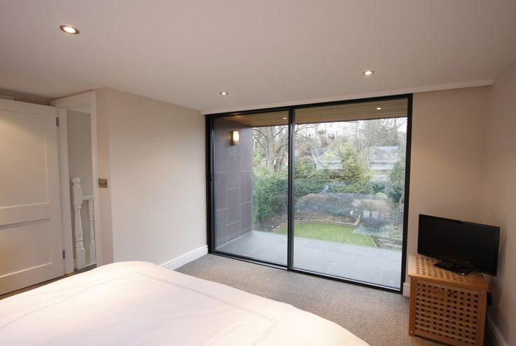 Slim framed sliding doors to bedroom by IQ Glass UK