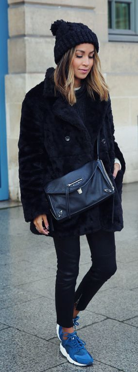 Julie Sarinana is wearing a black faux fur coat from Uniqlo, black jumper from Anine Bing, black skinny leather trousers from J Brand, the sneakers are from Nike and the bag is from Balenciaga