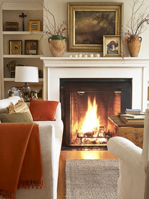 Gorgeous fall inspiration in this cozy living room with pumpkin spice hued  details, fire roaring in the fireplace, and autumnal vibes.