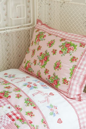 adorable mix of bedding, cottage style -- love the embroidery on the flat sheet header!