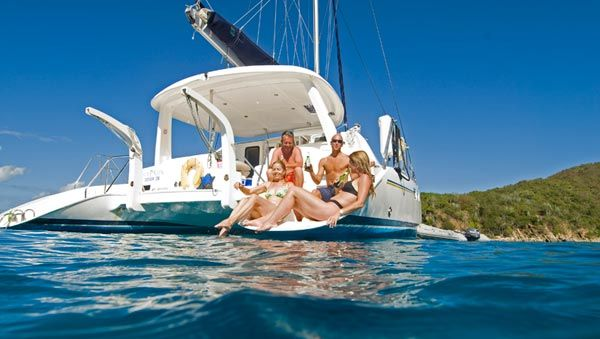 A photo of two couples relaxing on the back of a charter yacht
