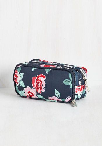 Whether you're planning a relaxing stay-cation or an overseas trip, this floral cosmetic case by LeSportsac is your must have accessory! Blossoming with a red and pink rose print, this navy pouch touts plenty of zippered pockets for storing your potions and powders in style.