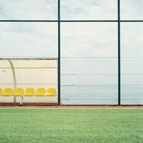 Beautiful photograph of a green tennis court and yellow seats. We're in the mood to play tennis today.
