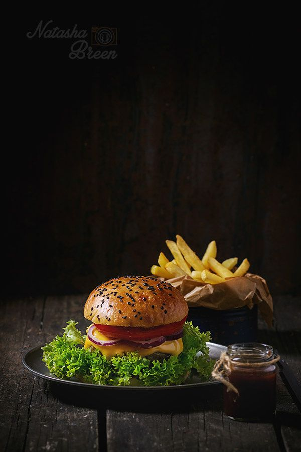 Homemade Hamburger - Fresh homemade hamburger with black sesame seeds in old metal plate with fried potatoes, served with ketchup sauce in glass jar over old wooden table with dark background. Dark rustic style.