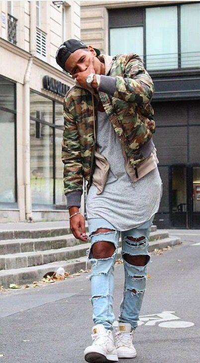 Um look urbano e moderno: Jaqueta militar, camiseta alongada, calça jeans  rasgada, tenis branco e boné snapback