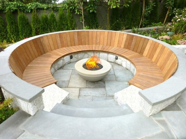 Feuerstelle umrundet von Sitzbank aus Holz im Garten