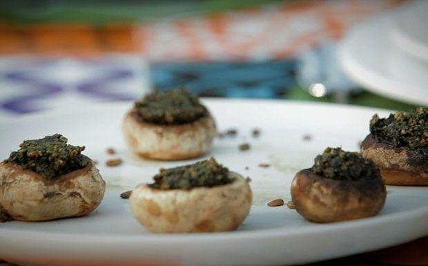 Ingredientes: 10 cogumelos frescos (portobelo mini ou paris) 1 xicara de manjericão 10 folhas de hortelã Azeite de oliva 1 punhado de sementes de girassol tostadas  Modo de preparo: Limpar os cogumelos um por um, com um pano úmido. Bater a folha, o azeite e as sementes no processador. Arrumar os cogumelos numa bandeja de cabeça para baixo e rechear com pesto. Levar ao forno (200ºC) por 20 minutos e servir.