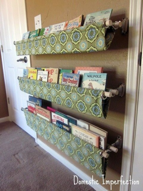 This looks like a super easy, shelf-less, way to hold all the kids books. Just dowel rods and curtain-rod holders. Pretty cool, and customizable as tastes change.