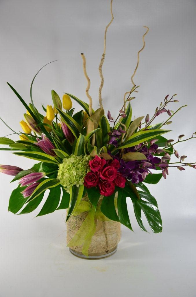 Vased arr of roses, tulips stargazer liles, dendrobium orchids and hydrangea. Monstera leaves and branches to accent
