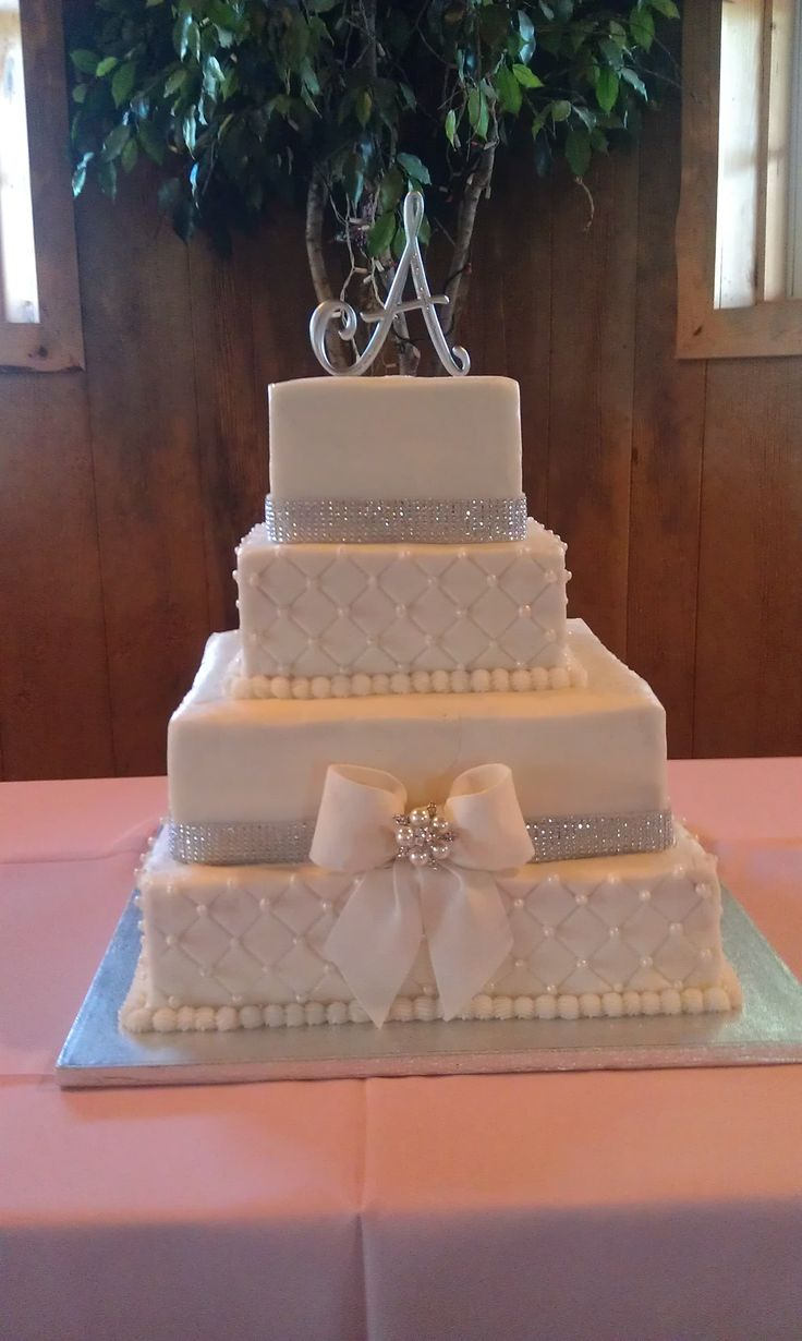 4 Tier Bling with Bow - Alternating layers of red velvet and strawberry cake frosted with buttercream. Bow is gumpaste.