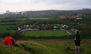 Fans watch the Whitehawk FC versus Lincoln City match from the hillside above The Enclosed Ground