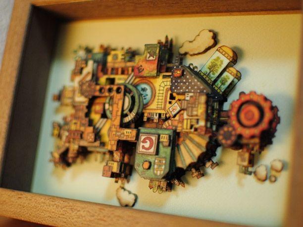 ユニ&ノナ 3次元BOX 「 ガジェットプラネット」  イラストレーターYuni&Nonaの3次元BOX(シャドーボックス)です。 イラストを重ねて、立体的な作品になっています。 一枚一枚手で切って手間ひまかけて作りました。 内寸:ポストカードサイズ(100mm×148mm), 外寸:額ブラウン(123mm×168mm)。 題名は「ガジェットプラネット」 昔の乗り物を組み合わせてできた 移動型住居星です。 別名「惑星G」 惑星なのでどちらが上でも下でも大丈夫です。 棚の上においたり、壁にかけたりできます。 おまけでYuni&Nonaポストカードが一枚ついてきます。