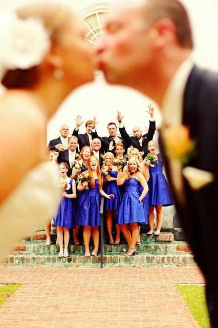 Bride & groom kissing (out of focus) and bridal party in focus. So cute!