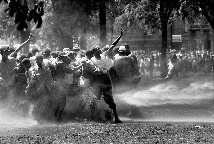 """Bob Adelman, the photographer who captured this image, described the scene at Kelly Ingram Park (Birmingham, Alabama): """"The police and firemen used a brute show of force to try to stop the ongoing demonstrations. It didn't work on this day. Rather than fleeing, the protesters hung on to each other and were able to stand up to the full fury of the water, though not without casualties. I have never witnessed such cruelty. There was almost as much moisture behind the lens as in front."""""""