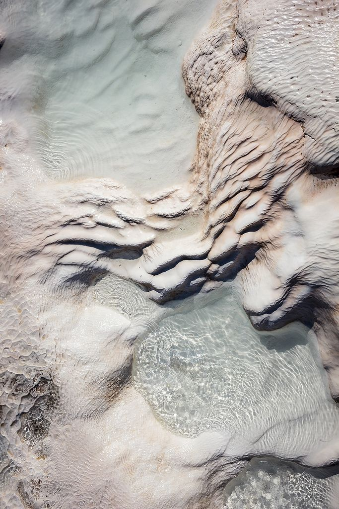 """Pamukkale, meaning """"cotton castle"""" in Turkish, is a natural site in Denizli Province in southwestern Turkey. The city contains hot springs and travertines, terraces of carbonate minerals left by the flowing water."""