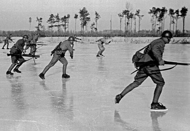 Dutch soldiers on ice-skates, 1940.  {The Waterline was a defensive line made up of dykes, flooded land and moats designed to protect the Netherlands from western attacks. The original Old Hollandic Waterline dated back to the 17th Century. It was rebuilt in the 19th Century after the Napoleonic wars and again modernized after WWI. During Winter soldiers would skate over the ice to pursue a retreating enemy}  [::SemAp::]