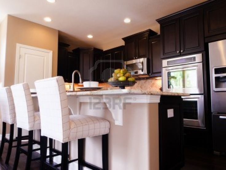 Modern kitchen with dark wood cabinets and hardwood floors. Stock Photo