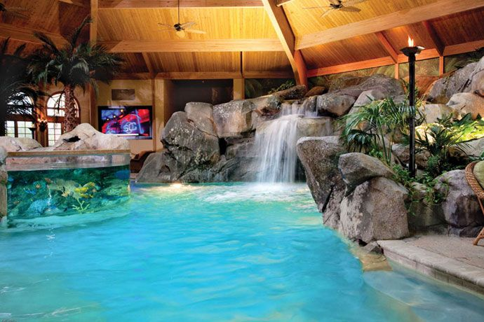 This massive backyard atrium features an indoor pool with a saltwater  aquarium, artificial palm trees, grotto waterfall, and big-screen TV!  Shehan