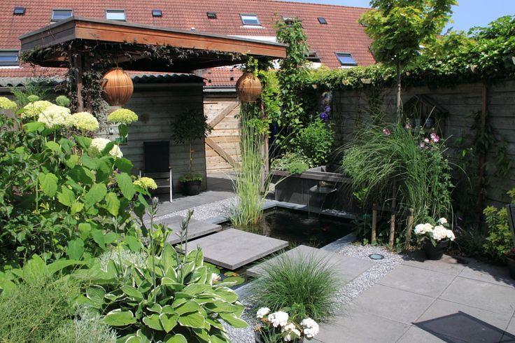 Klein afdak met lichtkoepel in kleine tuin. Deze tuin laat zien dat op een klein oppervlak toch veel mogelijk is.