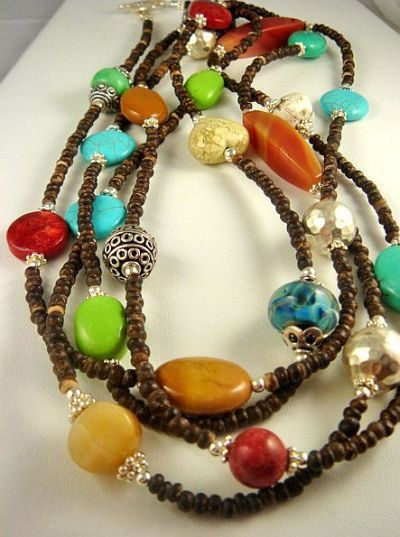 "This colorful necklace is made with 24 stones, artisan glass beads and sterling silver beads spaced between dark brown coconut shell rondelles. Approx 70"" long. A partial list of stones includes: wood jasper, picture jasper, red jasper, yellow jade, sponge coral, Chinese green turquoise, blue turquoise, honey jade, carnelian and white chalk turquoise."