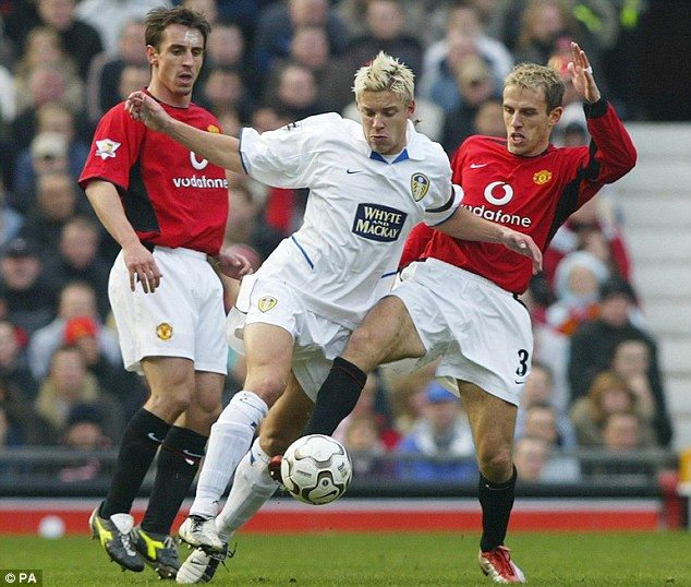 Phil tackles Leeds' Alan Smith as Gary looks on during a clash at Old Trafford in 2004