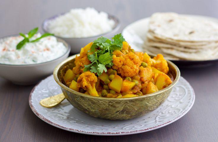 """Aloo gobi som betyder """"potatis blomkål"""" är namnet på en av de mest populära rätterna i Indien. Denna fantastiska gryta kan tillagas på många olika vis och är lika ljuvlig att serves med ris eller chapatibröd. Jag gillar gryta het med sting i, därför serverar jag raita bredvid. För att göra det helaännu lyxigareavrundar jag middagen med en iskall mango lassi. 4 stora eller 6 mindre portioner aloo gobi 1 blomkålshuvud 1 gul lök 4 st potatisar delade i tärningar 5 dl djupfrysta ärtor 1 msk…"""
