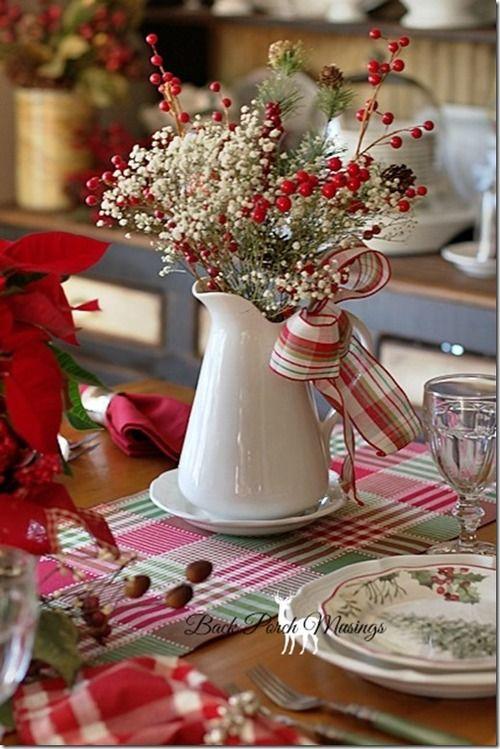 Use flores secas e fitas com estampa nas cores natalinas em um bule sobre a mesa.