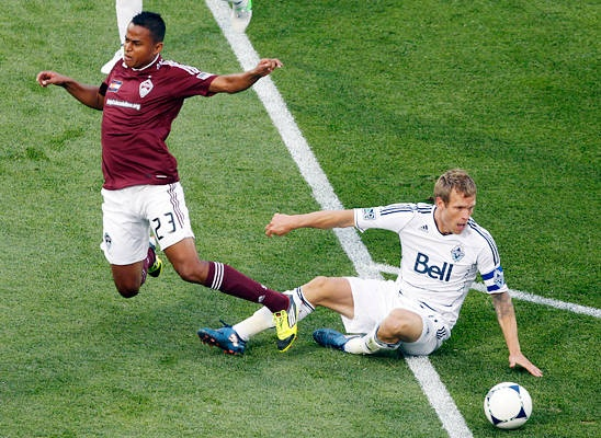 Colorado Rapids midfielder Jaime Castrillon, left, gets tangled up with Vancouver Whitecaps defender Jay DeMerit while pursuing the ball in the first half of a Major League Soccer game on Wednesday, July 4, 2012, in Commerce City, Colo.    David Zalubowski - AP Images