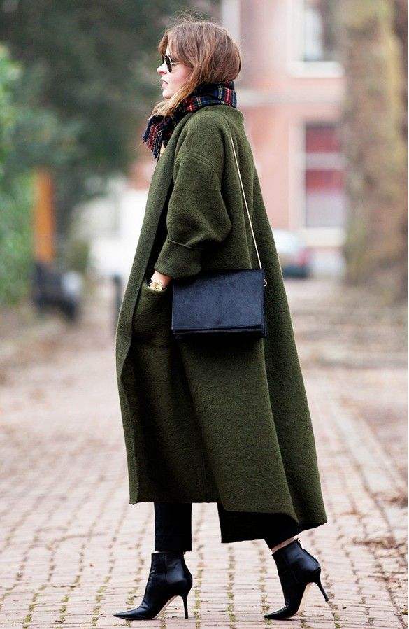 Christine Reehorst wears skinny jeans, a long olive green coat, a black shoulder bag, plaid scarf, aviator sunglasses, and black booties