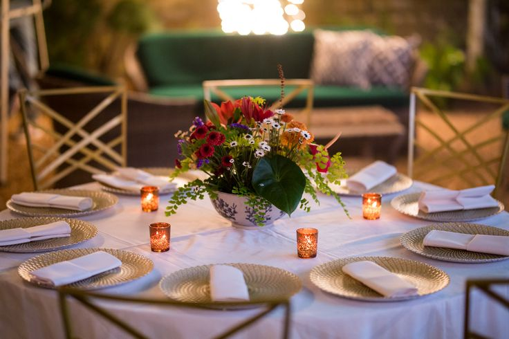Simple yet elegant Garden wedding table decor - multi colour flower arrangement with tropical leaves and maidenhair fern in Chinese blue and white porcelain bowl and golden charger plates on white table cloth.