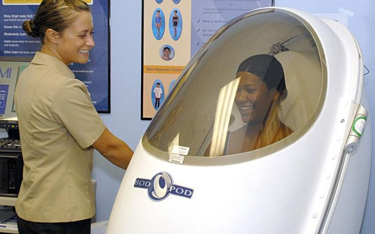 HM2 Sarah Weaver (left) uses a Bod Pod to capture body fat measurements of CS3 Michelle Pereira at Naval Hospital Jacksonville's Wellness Center. The Bod Pod uses air displacement to precisely measure the body's density, within a two percent margin of error, providing a more accurate weight assessment of patients.