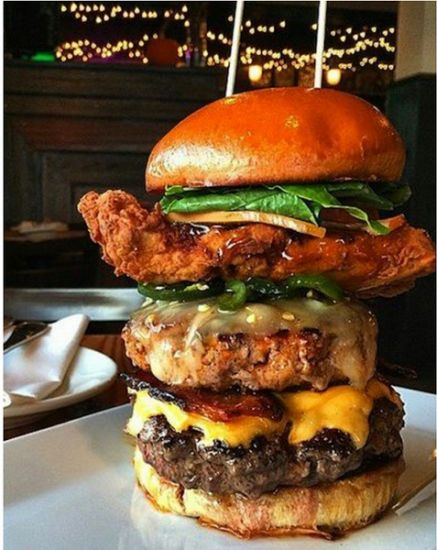 giant burger with fried chicken and toppings