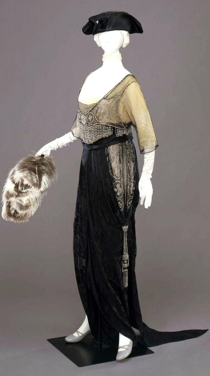 """Evening dress, Sartoria a la Ville de Lyon Raphael Goudstikker, Naples, ca. 1912. High-waisted black silk tulle embroidered w/geometric motifs in sequins, glass beads & jet on layer of ivory  tulle. V neckline in front; square in back, tight sleeves cut to elbow inside kimono sleeves. """"Culotte skirt"""" in black silk damask in design of water lilies, draped on sides & highlighted with embroidery, tassels, & rhinestones. Cut on bias; train. Galleria del Costume di Palazzo Pitti via Europeana…"""