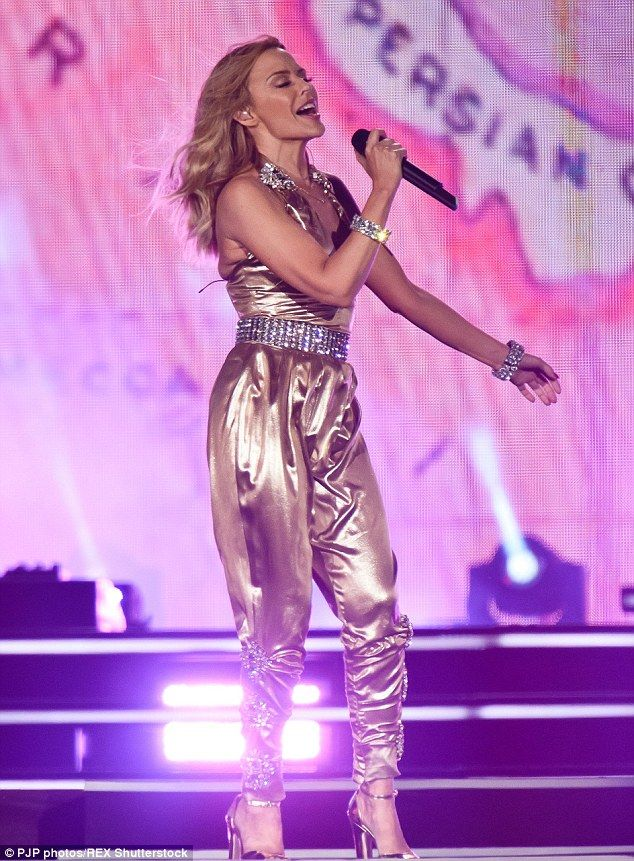 Standing tall: The petite singer wore a pair of chunky heeled sandals with the jewelled al...