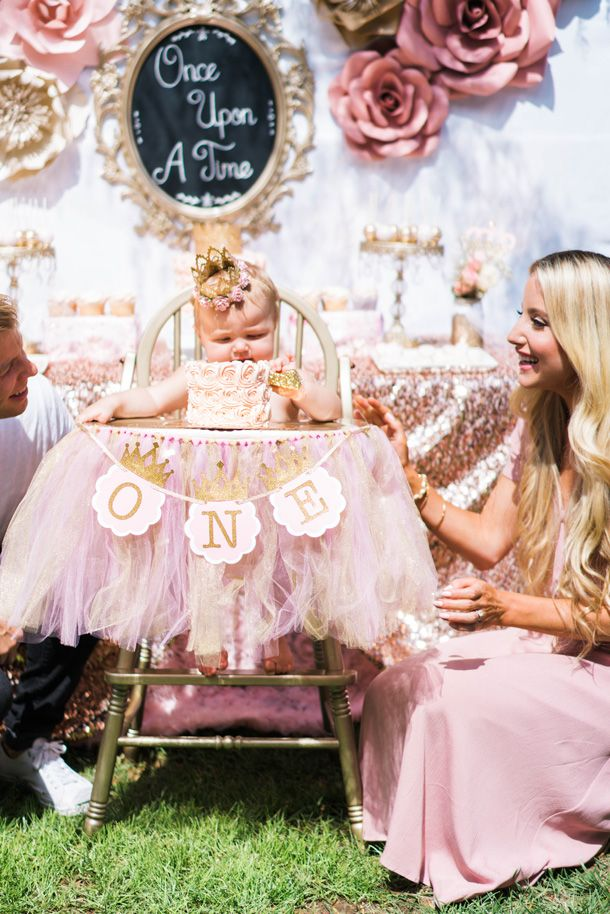 Once Upon A Time 1st Birthday Party idea. Cute pink and gold high chair decorations. Princess Party. Pink Princess smash cake with gold number 1 candle. Touch of Pink